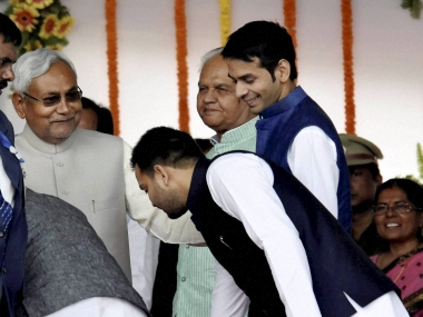 Patna: RJD chief Lalu Prasad's sons seeks blessings of Bihar Chief Minister Nitish Kumar during the later's swearing-in ceremony at Gandhi Maidan in Patna on Friday. PTI Photo  (PTI11_20_2015_000169B)
